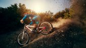 Man riding a mountain bike in downhill style at sunrise. Extreme sports on a bicycle. — ストック写真
