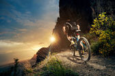 Cyclist riding mountain bike on trail at evening. — Stock Photo