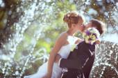 Wedding kiss in the rain — Stock Photo