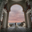 Wedding kiss under arch of the palace. — Stock Photo #53524833