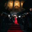 Woman in red dress on the red carpet photos of paparazzi — Zdjęcie stockowe #61415643