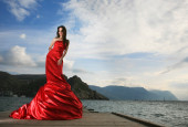 Beautiful young woman in red long dress outdoors. — Stock Photo