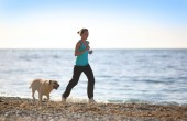 Woman running on the beach with a dog. Outdoor workout fitness. Training at sea. — Foto Stock