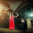 Woman in red dress posing in front of paparazzi — Stock Photo #62592787