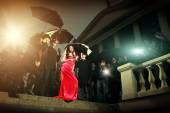 Woman in red dress posing in front of paparazzi  — Stock Photo