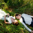Man and women lying on green grass and kissing. Spring wedding theme, young couple in love. — Stock Photo #70276203