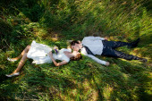 Man and women lying on green grass and kissing. Spring wedding theme, young couple in love. — Стоковое фото