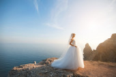 Beautiful young bride stands on rock in the sea rocky landscape — ストック写真