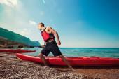 Kayaking. Man pulls kayak to shore beach. Leisure activities sea — Stock Photo