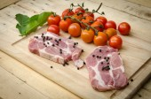 Pork and red tomato on kitchen board — Stock Photo