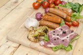 Fresh meat sausages  and vegetables on kitchen board — Stock Photo