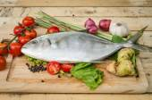Fish and vegetables on kitchen board — Stock Photo