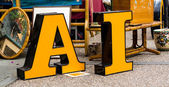 Big yellow letters at antique market  — Stock Photo