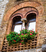 Floral old window of Tuscany town — Stock Photo