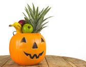 Halloween plastic pumpkin full of fruits — Stock Photo