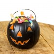 Black plastic pumpkin filled with candy wooden table — Stock Photo
