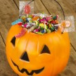 Halloween plastic pumpkin filled with candy on wooden table — Stock Photo