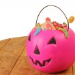 Pink plastic pumpkin filled with candy wooden table — Stock Photo #55018031