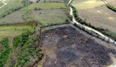 Aerial of gravel road, burned and green fields — Stock Photo