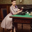 Pin Up beautiful young woman in vintage interior reading a book and prints on an old typewriter — Stock Photo #54507857