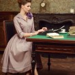 Pin Up beautiful young woman in vintage interior reading a book and prints on an old typewriter — Stock Photo #54507859