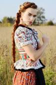 Young peasant woman, dressed in Hungarian national costume, posing over nature background — ストック写真