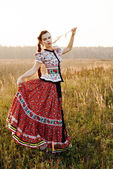 Young peasant woman, dressed in Hungarian national costume, posing over nature background — Stock Photo