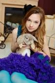A young girl in the image of Alice in Wonderland is sitting near the fireplace and holds the rabbit — Stock Photo
