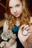 A young girl in the image of Alice in Wonderland holds the rabbit and pocket watches — Stock Photo