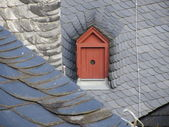 Attic window on the roof of a house for pigeons — Stock Photo
