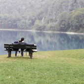 Lovers on the bench in front of the lake — Stock Photo