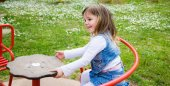 Little girl turns into a red carousel in an outdoor playground — Stock Photo