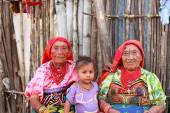 Playón Chico village, Panama - August, 4, 2014: Three generations of kuna indian women in native attire sell handcraft clothes to travelers, San Blas region, Panama. — Photo