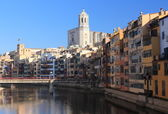Colorful houses placed close to the Onyar River with amazing cathedral's main tower on backwards, Girona, Spain. — Stock Photo