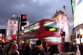 Piccadilly Circus, London -  February 14th of 2015: Lots of people, cars and typical red buses crossing the streets in this famous public space in London's West End that was built in 1819. — Stock fotografie