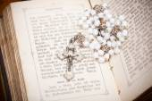 Rosary with jesus on crucifix on sides of opened bible, — Stock Photo