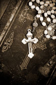 Ancient rosary on cover of old bible, closeup, textured background, sepia, — Stock Photo