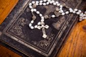 Rosary on cover of old black bible, wooden flooring, — Stock Photo