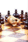 White Chess King checkmated by many opposing pawn, wooden chessboard — Stock Photo