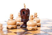 Chess King surrounded by opposing pawn, white background, copy space — Stock Photo