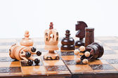 Chess Game with winning white King, surrounded by fallen queens, white background, copy space — Stock Photo