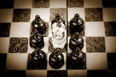 Chess King surrounded by group of opposing pawn, sepia, vintage — Stock Photo