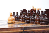 Courageous Pawn standing in front of opposing lineup, old wooden Chess Game — Stock Photo