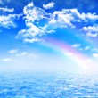 Colorful rainbow on blue summer sky with cumulus clouds over crystal clear water — Stock Photo #69303227