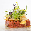 Appetizer with tartar of veal tenderloin, artichokes and fresh herb salad — Stock Photo #70122211