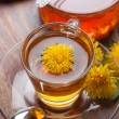 Herbal tea made of fresh dandelion essence, with honey, yellow blossoms and green leaf — Stock Photo #71251931
