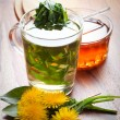 Herbal dandelion tea with fresh leaf in tea cup. on wooden table — Stock Photo #71252239