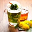 Herbal tea with dandelion tea in tea cup, honey and yellow blossoms on wooden table — Stock Photo #71252293