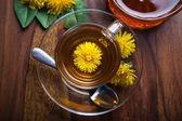 Dandelion herbal tea with fresh yellow blossom in tea cup, on wooden table — Stock Photo