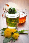 Herbal dandelion tea with fresh leaf in tea cup. on wooden table — Stock Photo